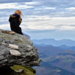 Woman sits on a cliff looking out Mindful Gratitude