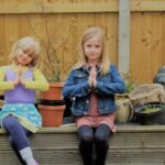 2 children practicing yoga with namaste in the garden together