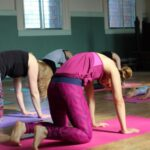 Yoga students practicing slow flow cat and cow pose at Yoga Space Leeds