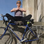 Yoga teacher sat in yoga pose with bike leeds