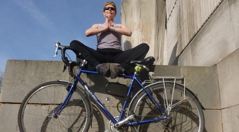 Yoga teacher sat in yoga pose with bike leeds